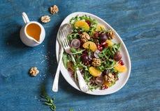 вкусный фруктовый салат Фруктовый салат виноградин, tangerine, гранатового дерева и arugula На голубой деревянной предпосылке, вз Стоковая Фотография