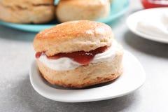 Вкусный scone с свернутыми сливк и вареньем на плите, крупном плане Стоковые Изображения RF