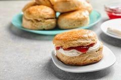 Вкусный scone с свернутыми сливк и вареньем на плите Стоковые Изображения