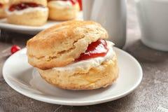 Вкусный scone с свернутыми сливк и вареньем на плите Стоковые Изображения RF