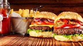 2 вкусных бургера с корзиной фраев и соуса Стоковые Изображения