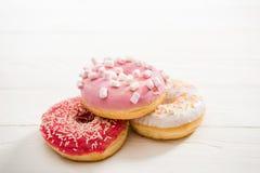 3 вкусных donuts с замораживать на верхней части лежа на деревянном столе аппетитная предпосылка donuts шоколада Стоковое Изображение