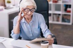 Включенная очаровывая постаретая женщина работая в офисе стоковые фотографии rf