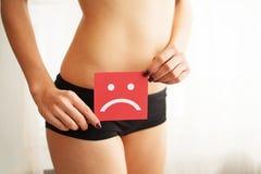 Влагалищная или мочевыделительная концепция инфекции и проблем Молодая женщина держит бумагу с грустной улыбкой над crotch стоковые изображения
