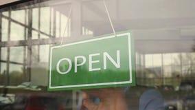 Владелец бизнеса поворачивает знак от закрытого раскрыть перед его магазином сток-видео