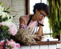 Владелец магазина говоря на телефоне и принимая примечание стоковые фото