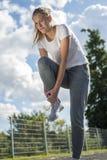 Владение бегуна молодой женщины ее нога спорт раненая стоковые фото