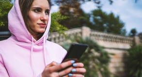 Владение девушки в руках мобильном телефоне, типе сообщении человека на смартфоне, ослабляет туристские перемещения планируя откл стоковые фото