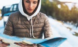 Владение девушки в руках смотря на карте, ослабляет туристские перемещения автоматическим автомобилем, отключение людей планируя  стоковая фотография