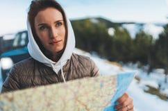 Владение девушки в руках смотря на карте, ослабляет туристские перемещения автоматическим автомобилем, отключение людей планируя  стоковые фотографии rf