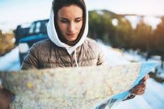 Владение девушки в руках смотря на карте, отключении людей планируя в горе снега, ослабляет туристские перемещения автоматическим стоковое изображение