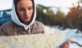 Владение девушки портрета в руках смотря на карте, ослабляет туристские перемещения автоматическим автомобилем, отключение людей  стоковая фотография