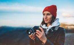 Владение девушки хипстера туристское в руках принимает фотографию нажимает на современной камере фото, взгляде фотографа на техно стоковое изображение