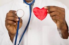 Владение знахаря в сердце рук в красных игрушке и стетоскопе стоковые фото