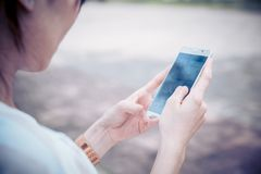 Владение руки женщин 2 крупного плана используя smartphone стоковые фото