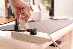 Владение руки женщин электрическая штепсельная вилка к установке на соединение электроснабжения Стоковое фото RF