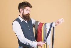 Владение хипстера человека бородатое немногие галстуки Гай с бородой выбирая галстук Идеальный галстук Отборная связь которой име стоковые изображения rf