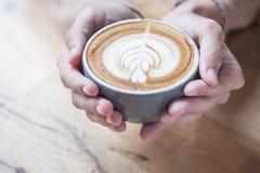 Владение чашки кофе на руках women's которые имеют верхнюю часть вспененный Стоковая Фотография RF