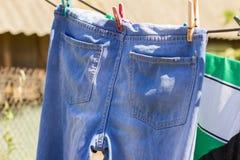 Влажные голубые джинсы вися на веревочке стоковое фото