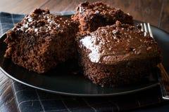 Влажные части пирожного торта губки шоколада в черной плите Стоковая Фотография