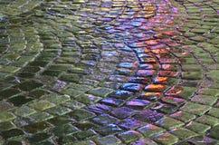 Влажный булыжник с синью и красные светы отразили дождевой водой стоковое фото rf