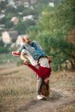 Влюбленнаяся пара стоит, смеется над жизнерадостно и disports на лесе стоковые фотографии rf
