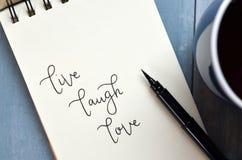 ВЛЮБЛЕННОСТЬ В РЕАЛЬНОМ МАШТАБЕ ВРЕМЕНИ СМЕХА рук-lettered в блокноте с ручкой щетки стоковое фото rf