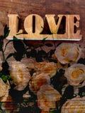 Влюбленность искусства, знака влюбленности на винтажной предпосылке деревянных и белых роз стоковое фото