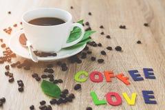 Влюбленность кофе рассказа и белая кофейная чашка в утре на деревянном ба Стоковое Изображение RF
