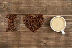 влюбленность кофе i Кофейные зерна и чашка Coffe на таблице Стоковое фото RF
