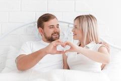 Влюбленность, люди и концепция счастья - усмехаясь пара в кровати, вручает делать форму сердца Стоковое Изображение RF