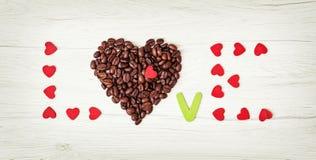 ВЛЮБЛЕННОСТЬ названия кофейных зерен и много маленьких красных сердец на сватать Стоковые Фотографии RF