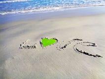 ВЛЮБЛЕННОСТЬ написанная на пляже Стоковые Фотографии RF