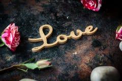 ВЛЮБЛЕННОСТЬ, сердца и цветки слова Стоковая Фотография