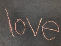 Влюбленность слова, написанная в розовом меле тротуара Стоковые Фото