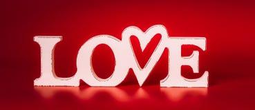 Влюбленность слова на красной предпосылке, вид спереди Стоковые Фото
