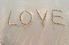 ВЛЮБЛЕННОСТЬ слова на песке пляжа Стоковые Изображения RF