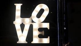 ВЛЮБЛЕННОСТЬ слова украшает свет приведенный в улице на ноче сток-видео