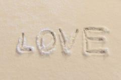 ВЛЮБЛЕННОСТЬ текста сочинительства на снеге Стоковая Фотография