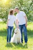 Влюбленныеся люди идут с собакой в сельской местности стоковая фотография rf