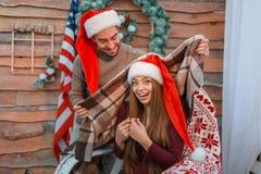 Влюбленныйся парень покрывает его девушку с одеялом, которое сидит в стуле indoors стоковые фотографии rf