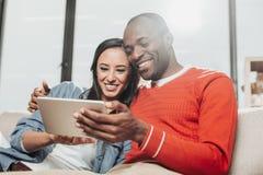 Влюбленныйся радостный мужчина и женское сидя и держа устройство Стоковые Изображения