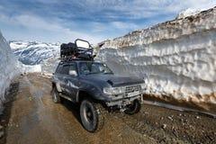Внедорожный крейсер земли Тойота автомобиля экспедиции управляя на дороге горы в тоннеле снега окруженном высокими сугробами стоковая фотография