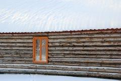 Внесите стену, окно и покрытую снег крышу в журнал дома в деревне Стоковые Изображения