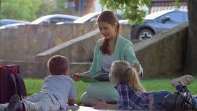 Внеучебные деятельности, милые дети слушая книгу чтения женщины после школы сидя на зеленой траве в природе внутри видеоматериал