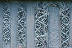 Внешней деревянной украшение высекаенное стеной средневекового Urnes ударяет церковь при мотивы Викинга покрытые с смолкой в Orne стоковые изображения rf