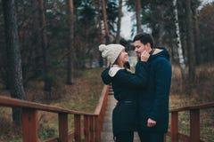 Внешние любящих молодых пар счастливые совместно на уютном греют прогулку в лесе стоковые изображения