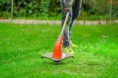 Внешний взгляд джинсов и использования молодого работника нося травы вырезывания косилки триммера лужайки в запачканной предпосыл Стоковые Фотографии RF