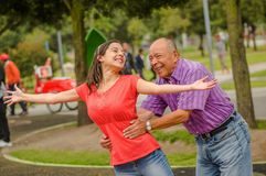 Внешний взгляд дочери и отца играя на outdoors в парке держа ее талию Стоковое Изображение