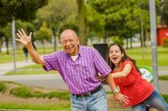 Внешний взгляд дочери и отца играя на outdoors в парке Стоковое фото RF